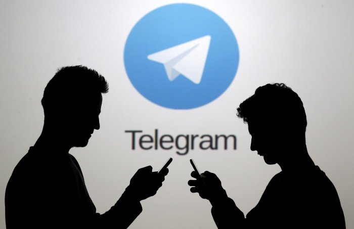 FILE PHOTO: Men pose with smartphones in front of a screen showing the Telegram logo in this picture illustration